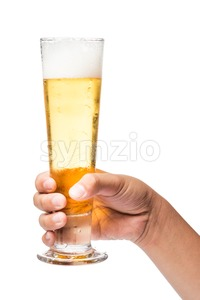 Hand holding a tall glass of beer with head foam ready toast cheers Stock Photo