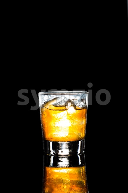 Whiskey on the rock in portrait orientation on a dark background Stock Photo