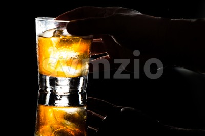 Hand reaching for glass of whiskey on the rocks on dark background Stock Photo
