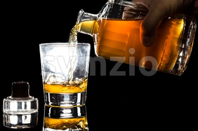 Hand pouring whiskey into a glass within dark background Stock Photo
