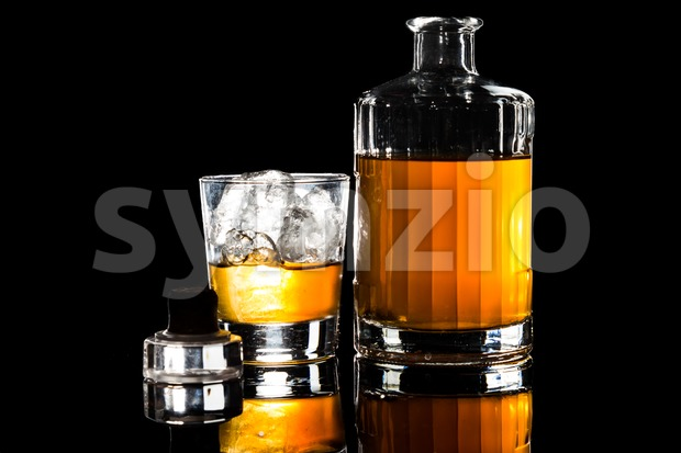 Whiskey on the rocks and a whiskey bottle in dark background Stock Photo
