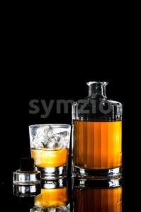 Whiskey on the rocks and a whiskey bottle on portrait format in dark background Stock Photo