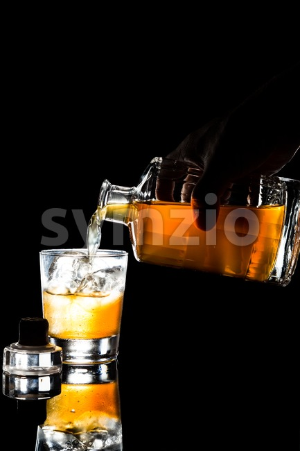 Hand pouring whiskey into a glass within dark background in portrait orientation Stock Photo