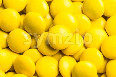 Close up on pile yellow milk chocolate candies crisp shell Stock Photo