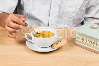 Person adding butter to coffee with milk, new diet that favor high amount of fat low carbo or ketogenic diet Stock Photo