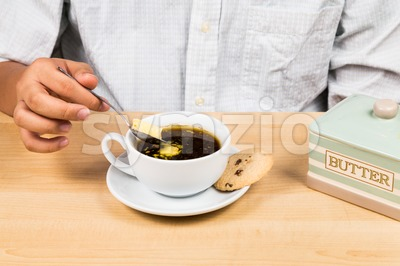 Person adding butter to back coffee, new diet that favor high amount of fat low carbo or ketogenic diet Stock Photo