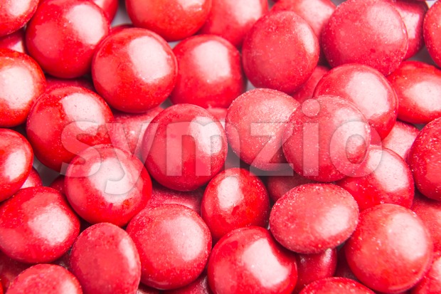 Close up on pile red milk chocolate candies crisp shell Stock Photo
