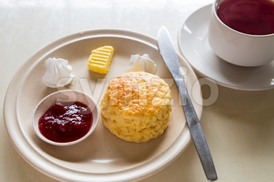 English scones set with a cup of tea served on a table next to window Stock Photo
