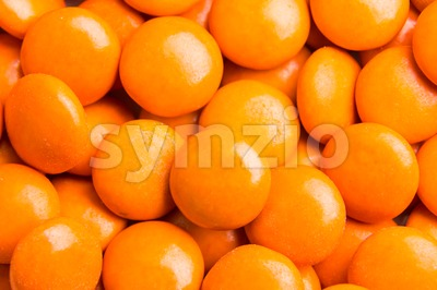 Close up on pile orange milk chocolate candies crisp shell Stock Photo