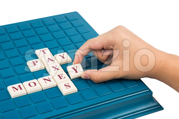 Concept of MONEY, PAY, TAXES crosswords on a board game Stock Photo