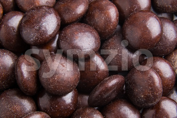Close up on pile brown milk chocolate candies crisp shell Stock Photo