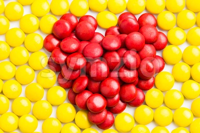 Heart shape red milk chocolate candies with yellow candies background Stock Photo