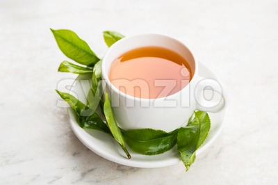 Brewed black tea rich with anti-oxidant. Freshly harvested tea leafs as props Stock Photo