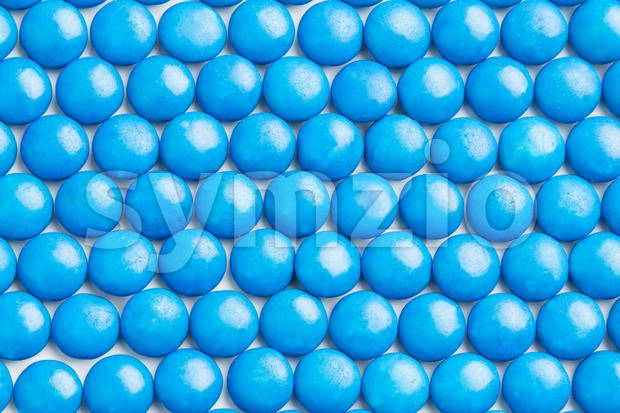 Close up neatly arranged blue milk chocolate candies crisp shell Stock Photo