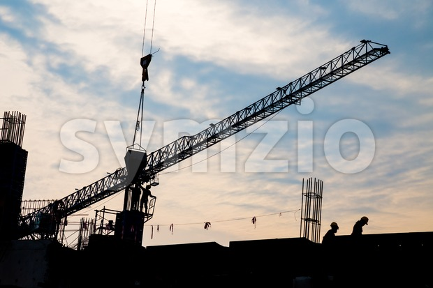 Silhouette image of workers working at construction site with tower crane Stock Photo