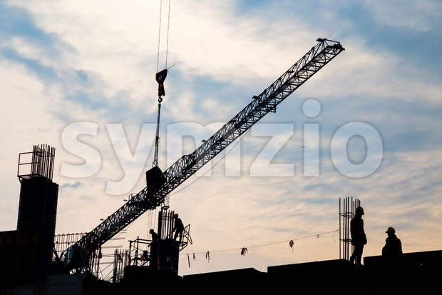 Silhouette image of workers working at construction site with tower crane