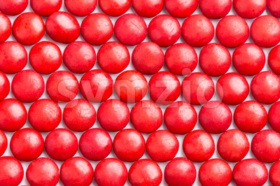 Close up neatly arranged red milk chocolate candies crisp shell Stock Photo