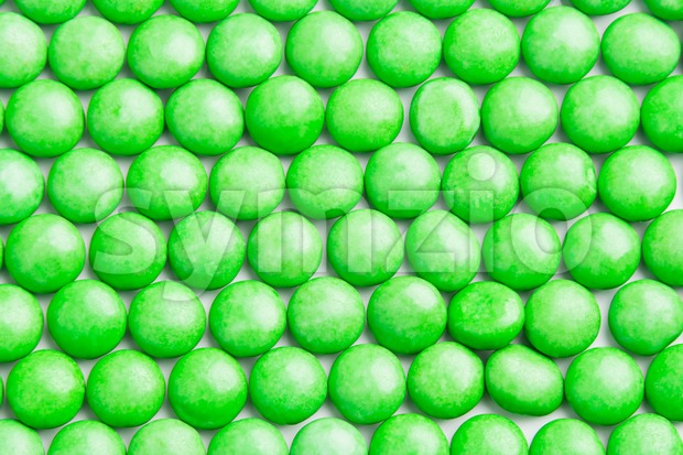 Close up neatly arranged green milk chocolate candies crisp shell Stock Photo