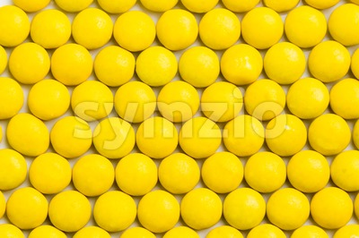 Close up neatly arranged yellow milk chocolate candies crisp shell Stock Photo