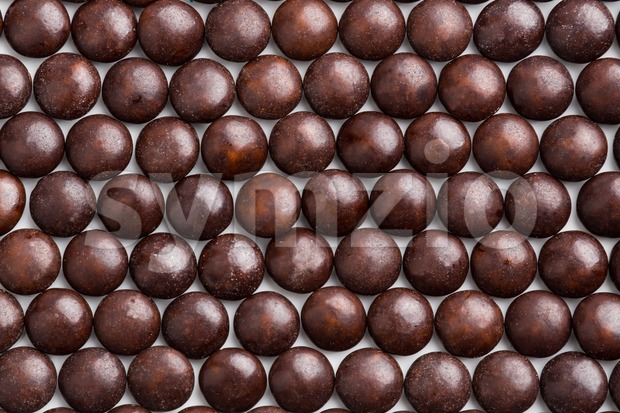 Close up neatly arranged brown milk chocolate candies crisp shell Stock Photo