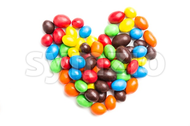 Heart shape with colorful milk chocolate candies on white background Stock Photo