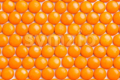 Close up neatly arranged orange milk chocolate candies crisp shell Stock Photo