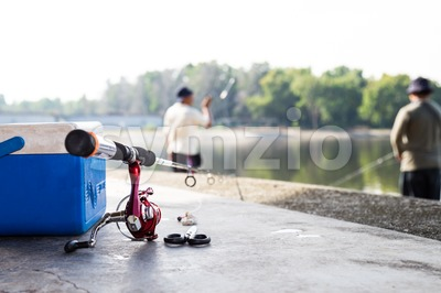 Fishing rod and tool box with anglers having recreation fishing at background Stock Photo