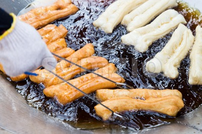 Deep frying bread stick or popularly known as You Tiao, a popular Chinese delicacy Stock Photo