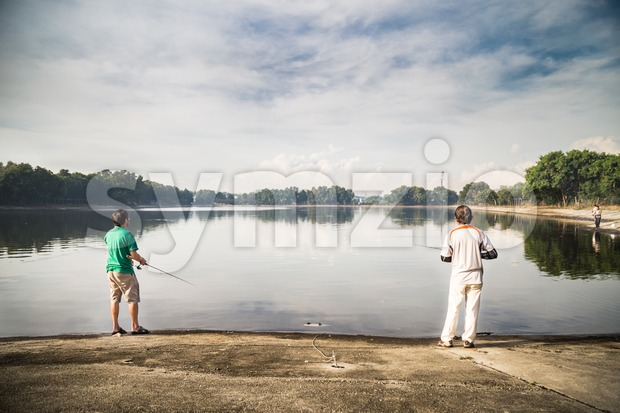 Recreational fishing at a lake with serene view  in a beautiful morning Stock Photo
