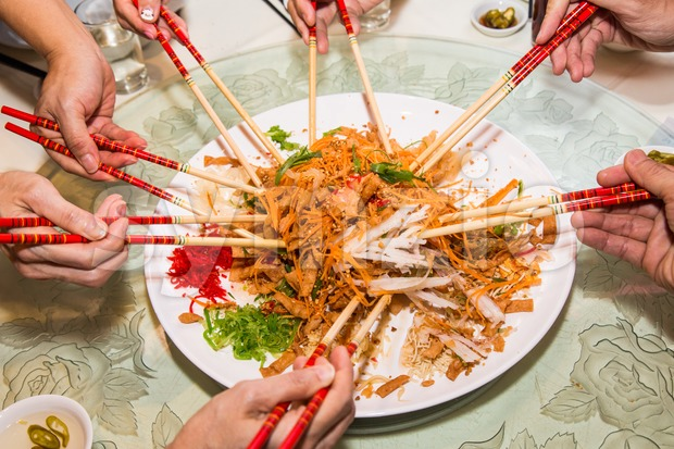 A group of people mixing and tossing Yee Sang dish with chop sticks. Yee Sang is a popular delicacy taken during Chinese New Year, believed to bring Stock Photo