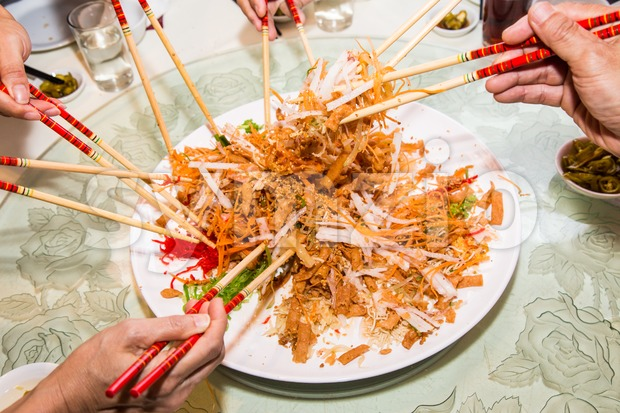 A group of people mixing and tossing Yee Sang dish with chop sticks. Yee Sang is a popular delicacy taken ...
