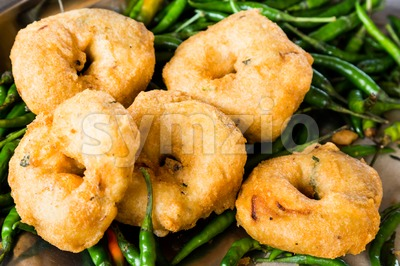 Uluntu Vadai with green chili pepper, a popular Southern Indian deep fried snack Stock Photo