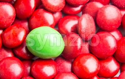 Focus on green chocolate candy against heaps of red candies Stock Photo