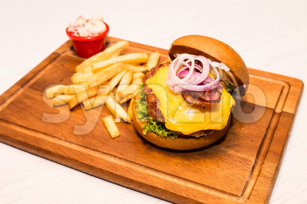 Close up on delicious Pork burger with cheese, vegetable and served with fries