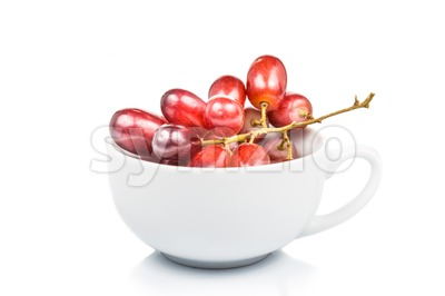 A cup of sweet and juicy red crimson grape isolated in white Stock Photo