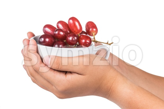 Hand holding cup full of sweet and juicy red crimson grapes Stock Photo
