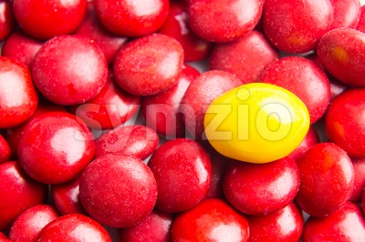 Focus on yellow chocolate candy against heaps of red candies Stock Photo