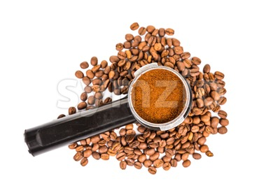 Coffee portafilter filled with finely grounded coffee, and with coffee beans scattered around Stock Photo