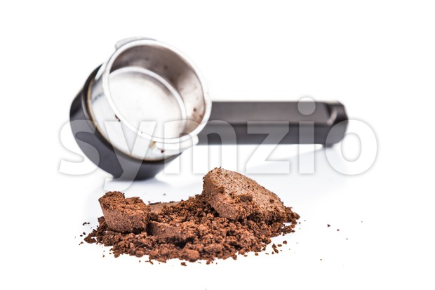 Spent or used coffee grounds with portafilter in the background Stock Photo