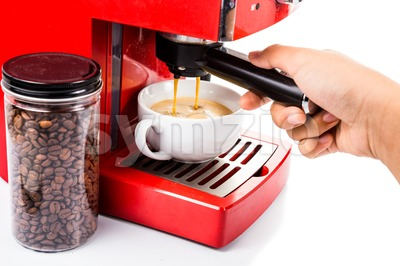 Hand operating red color coffee machine brewing espresso Stock Photo