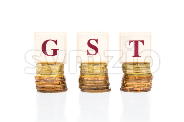 GST concept with stack of coins and letters Stock Photo