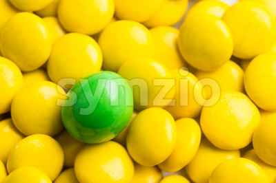 Focus on green chocolate candy against heaps of yellow candies Stock Photo