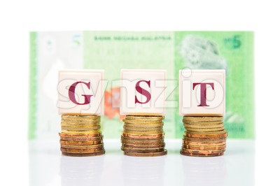 GST or Good and Services Tax concept with stack of coins and Malaysian Ringgit as backdrop Stock Photo