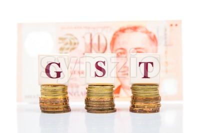 GST or Good and Services Tax with stack of coins and Singapore Dollar as backdrop Stock Photo