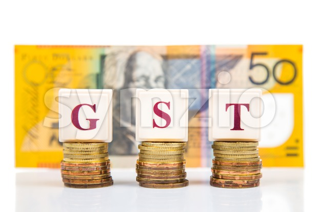 GST or Good and Services Tax concept with stack of coin and Australian Dollar as backdrop Stock Photo