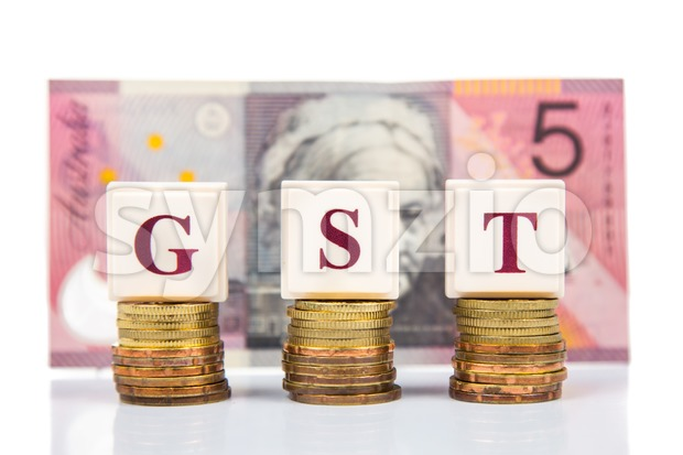 GST or Good and Services Tax concept with stack of coin and Australian Dollar as backdrop