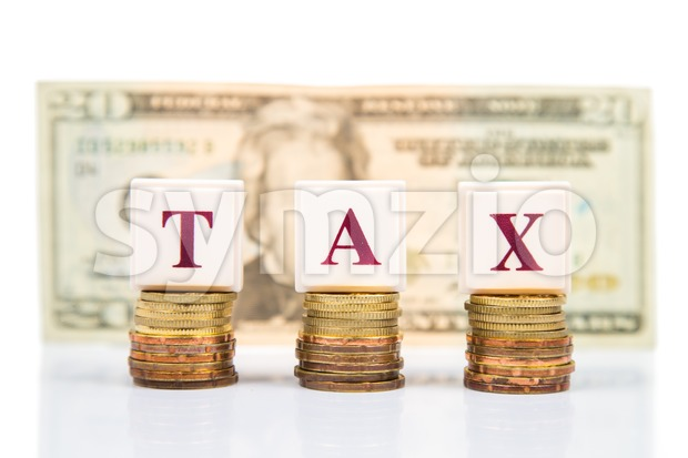 Tax concept with stack of coin and US Dollar as backdrop Stock Photo