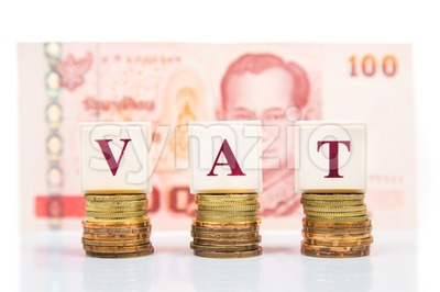 VAT or Value Added Tax concept with stack of coins and Thai Baht as backdrop Stock Photo