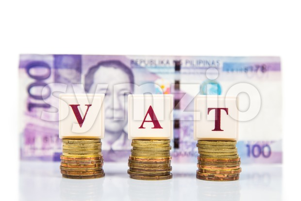 VAT or Value Added Tax concept with stack of coin and Philippines Piso as backdrop Stock Photo