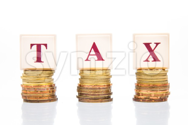 TAX concept with stack of coins and letters Stock Photo